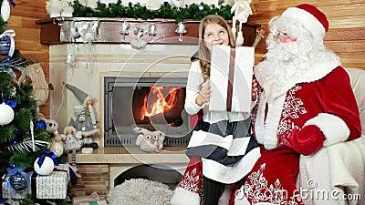 Санта дает подарок девушки, счастливый усмехаясь ребенка, желания приходит торжество верно, Нового Года и рождества акции видеоматериалы
