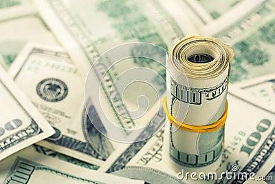 Свернутый $100 долларовым банкнотам