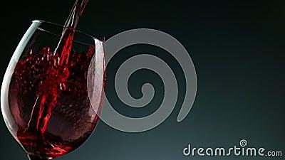 Сверхмедленный съемный выстрел красного вина из бутылки на темном фоне сток-видео