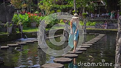 Сдвиг фильма о молодой туристке, посетившей водный дворец Тирта Гангга, бывший королевский дворец на острове Бали акции видеоматериалы