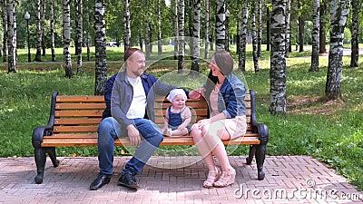 Семейный портрет: мама, папа сидят на скамейке в городском парке и разговаривают с маленькой девочкой акции видеоматериалы