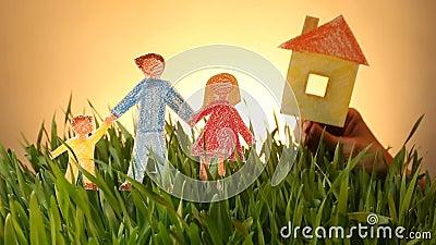 Семья и нарисованный домом значок на предпосылке лета зеленого цвета травы сток-видео