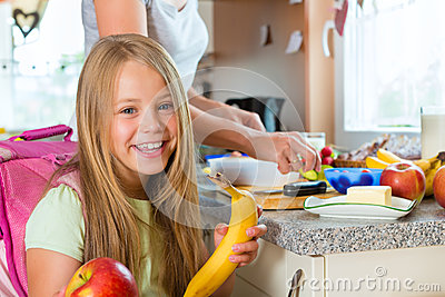 Семья - мать делая завтрак для школы