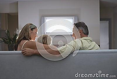 Семья смотря TV дома