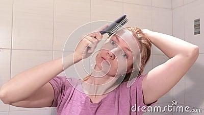 Середина постарела белокурая женщина чистя ее влажные волосы щеткой с brusher волос в bathroom видеоматериал