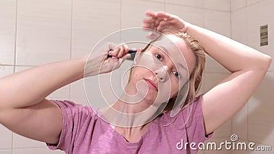 Середина постарела белокурая женщина чистя ее влажные волосы щеткой с brusher волос в bathroom сток-видео