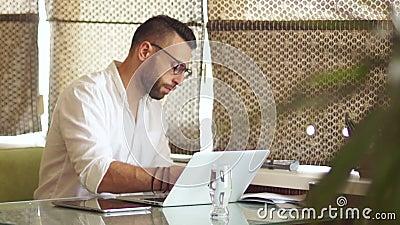 Серьезный молодой бизнесмен в белой рубашке на работе в офисе Уютный внутренний coworking Свободная занятость сток-видео