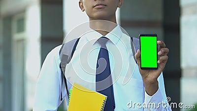 Серьезный ученик, показывающий мобильный телефон, приложения для зачисления в специализированную школу видеоматериал