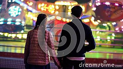 Силуэт пар, которые стоящ назад к камере и наблюдая вращению привлекательностей в парке атракционов Любовники сток-видео