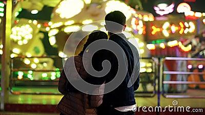 Силуэт пар, которые стоящ назад к камере и наблюдая вращению привлекательностей в парке атракционов Любовники видеоматериал