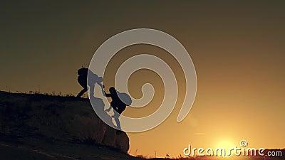 Силуэт руки помощи между альпинистом 2 2 hikers na górze горы, человек помогают человеку взобраться отвесная видеоматериал