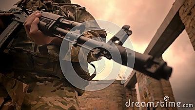 Сильный подлинный солдат стоит уверенно и держит автоматическое оружие, на открытом воздухе, разрушенное здание, пустой космос сток-видео