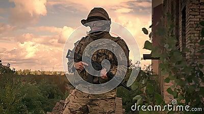 Сильный подлинный солдат стоит resistantly нося камуфлирование и шлем с автоматическим оружием в руках, freen сток-видео
