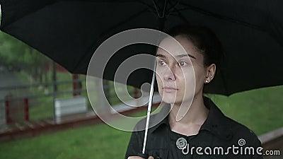 Сиротливая унылая женщина идет вниз с улицы в проливном дожде движение медленное акции видеоматериалы