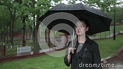 Сиротливая унылая женщина идет вниз с улицы в проливном дожде движение медленное сток-видео