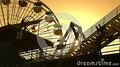 Силуэт езд парка атракционов с Солнцем сток-видео