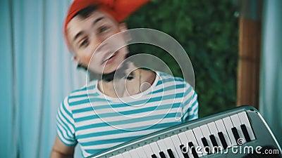 Смешной одетый человек по мере того как бородатый карлик играет синтезатор и голову встряхивания сток-видео
