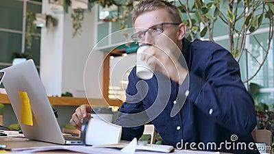Смешной шальной программист с кофе наркомании кофеина выпивая и печатать быстро на компьтер-книжке в офисе 4K акции видеоматериалы