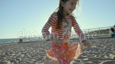 Смеясь над малая девушка бежит вдоль пляжа моря пока спотыкающся в песок в slo-mo акции видеоматериалы
