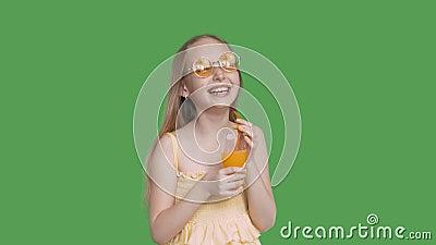 Смеясь удерживание девушки в стекле апельсинового сока рук на прозрачной зеленой предпосылке Счастливый подросток девушки в желты видеоматериал