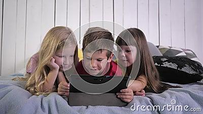 Современное детство, маленькие друзья в разноцветных футболках используют цифровые планшеты и чат, лежа дома в постели видеоматериал