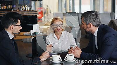 Согласование жизнерадостной дамы дела обсуждая с мужскими партнерами встречая в кафе видеоматериал