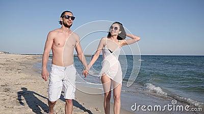 Соедините романтичную прогулку на пляже, людях любовников идя вокруг руки barefoot на песок, лето, пару в влюбленности, экзотичес сток-видео