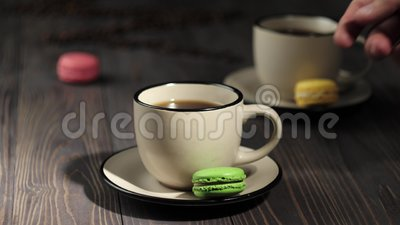 Состав из кофейни Деревянный стол, украшенный кофе-бобами, цветными макаронами и чашками с кофе акции видеоматериалы