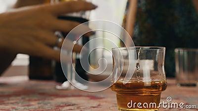Спирт питья людей на террасе Человек льет стекло коньяка вкратце на таблице cheer сток-видео