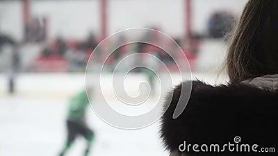 Спичка хоккея excited женского сторонника наблюдая, командные игроки катаясь на коньках на катке видеоматериал