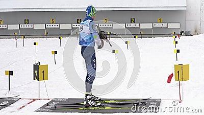 Спортсмен-биатлонист стреляет, стреляет из винтовки и перегоняет винтовку на позиции Соревнования среди юниоров по биатлону 'Вост сток-видео