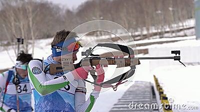 Спортсмен, стрелка из винтовки, перезаряжающая винтовка на позиции Биатлетт Русинов Владислав сток-видео
