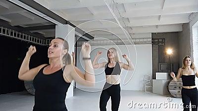 Спорт и здоровый уклад жизни Группа в составе атлетические девушки в черных bodysuits выполняет шаг подогрева аэробный в студии ф сток-видео