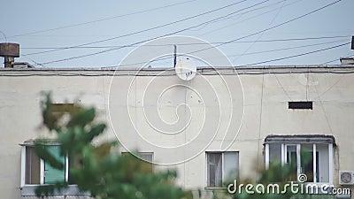 Спутниковая антенна-тарелка на стене многоэтажного здания видеоматериал