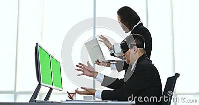 Средн-достигшие возраста бизнесмены сидя и осматривая содержание прибора виртуальной реальности сток-видео