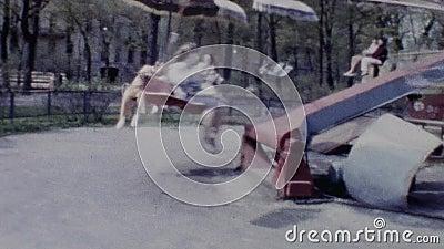 Старая винтажная цветная пленка parents при дети ехать carousel в парке атракционов видеоматериал