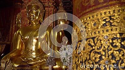Старое большое позолоченное Buddhas усаженное на поднятую платформу внутри виска Wat Phumin акции видеоматериалы