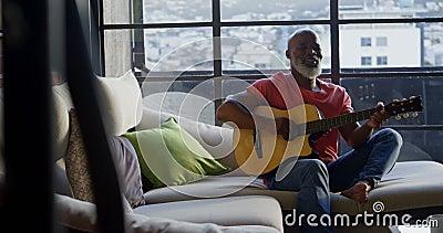 Старший человек играя гитару дома 4k видеоматериал