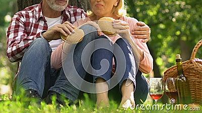 Старые пары есть бургеры outdoors, холестерол роста высококалорийной вредной пищи, здравоохранение сток-видео