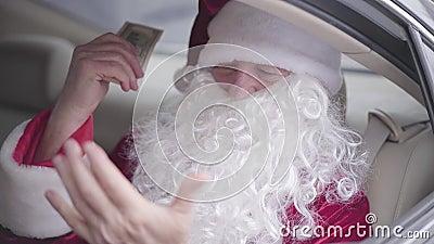Старый Санта Клаус, сидящий в машине на заднем сиденье, нюхая долларовую пачку и улыбаясь, затем поднимает стекло, прячась акции видеоматериалы