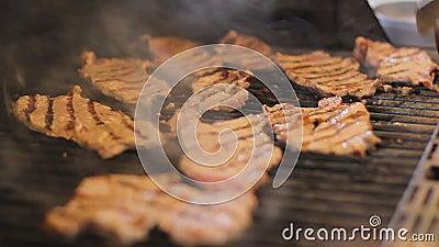 Стейки мяса сварены на гриле газа Вкусные мясные блюда на открытом воздухе Дым приходит от еды Кашевар поворачивает говядину акции видеоматериалы