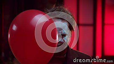 Страшный клоун, выглядящий из красного шара и жутко улыбающийся - мигающий мигающий мигающий свет акции видеоматериалы