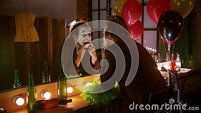 Страшный клоун, показывающий сумасшедшие эмоции, кладёт пальцы в рот и улыбается видеоматериал