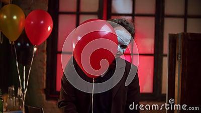 Страшный клоун, слегка выглядящий из красного шара и жутко улыбающийся видеоматериал