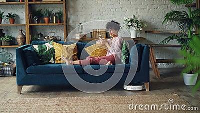 Студентка использует smartphone ослабляя на софе пока робототехнический hoover очищает пол в доме электрическо видеоматериал