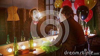 сумасшедший клоун смеется над собой в зеркале, выкрашенный голубым языком, размазая волосы и сходя с ума акции видеоматериалы