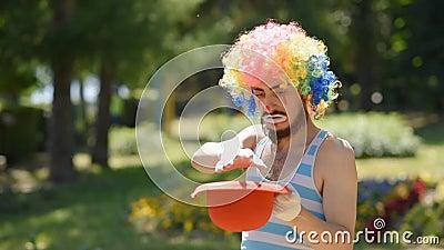 Сумасшедший mime показывает фокус с красной шляпой и фиг в парке Клоун показывает набросок на улице видеоматериал