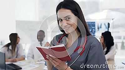 Сфокусированный кавказский женский доктор делая некоторое примечание в тетради пока команда штата говоря на предпосылке внутри сток-видео