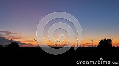 Сценарий силуэта с ветряными турбинами для производства электроэнергии экологически и экологически чистой энергии в закатной атмо акции видеоматериалы