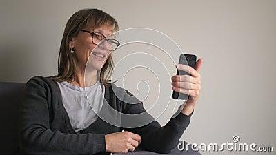 Счастливая взрослая женщина со средним возрастом, держащая смартфон с видео-чатом, использующая приложения в социальных сетях в т видеоматериал